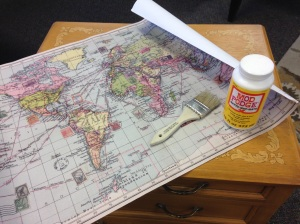 Preparing to 'ModPodge' the map to the table surface.